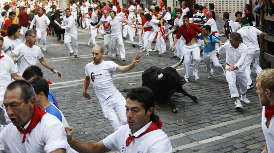 Victoriano del Rio fighting bull falls next to runners at Estafeta corner during the sixth running of the bulls at the San Fermin festival in Pamplona.