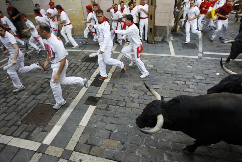 Runners sprint ahead of Victoriano del Rio fighting bulls at Estafeta corner during the sixth running of the bulls at the San Fermin festival in Pamplona