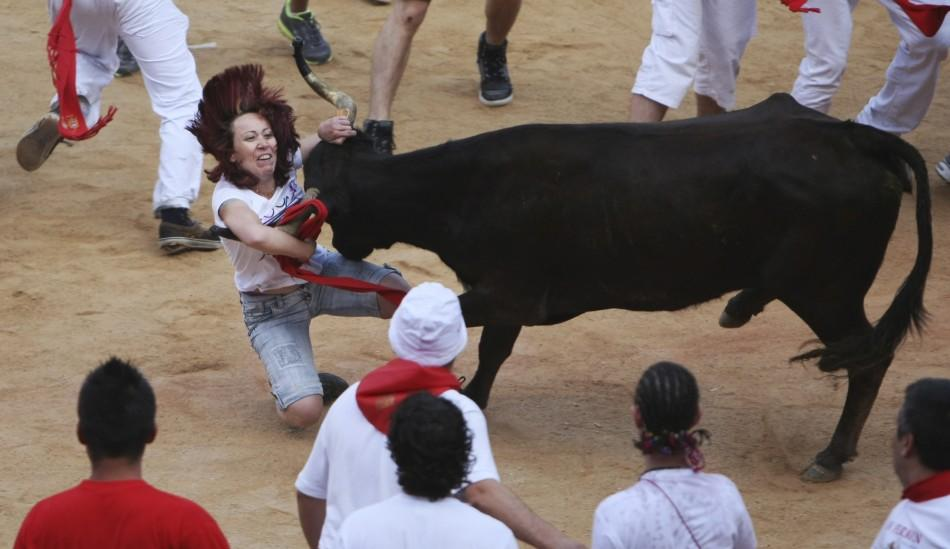 A heifer charges at a reveller at Pamplona's bullring after the sixth running of the bulls at the San Fermin festival in Pamplona