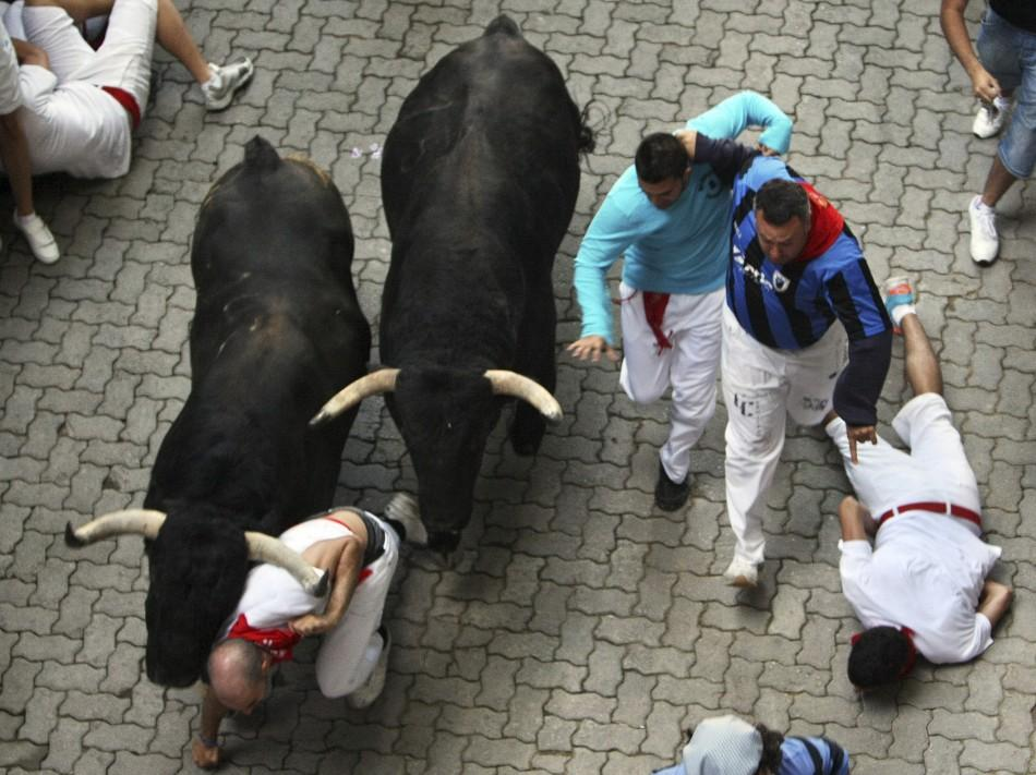 A runner falls in the way of two Victoriano del Rio fighting bulls at the entrance to the bullring during the sixth running of the bulls at the San Fermin festival in Pamplona