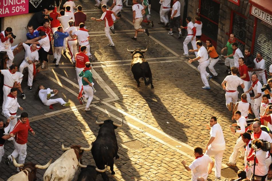 Victoriano del Rio fighting bulls cross the town hall square during the sixth running of the bulls at the San Fermin festival in Pamplona.
