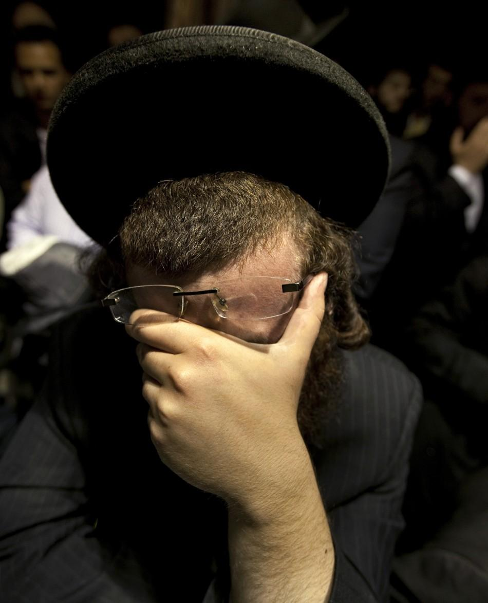 A man weeps while listening to the funeral of Leibby Kletzky in the Brooklyn borough of New York