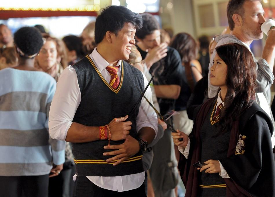 "Niko Evangelista (L) and Windy Rapanakul (R) join the crowds lined up to be the first to see the new Harry Potter movie ""Harry Potter and the Deathly Hallows - Part 2"" at a minute after midnight in the Hollywood area of Los Angeles, California"