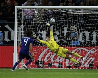 Japan's Saki Kumagai (L) scores the winning penalty
