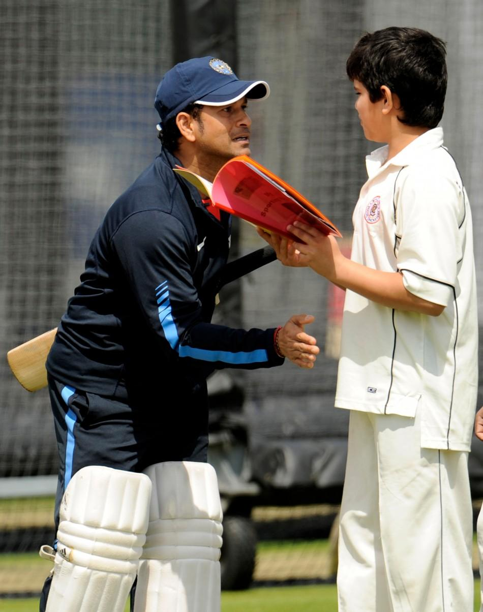 India's Tendulkar pats his son Arjun during a training session before Thursday's first cricket test match against England at Lord's cricket ground in London.