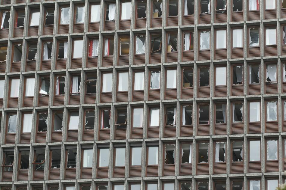 Broken windows of a government building are seen after a powerful explosion rocked central Oslo