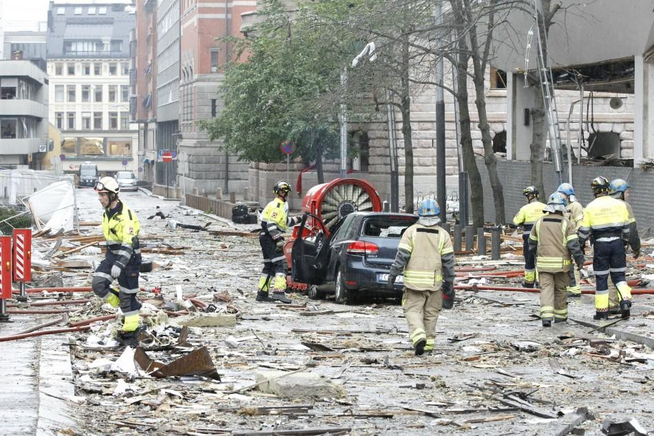 Rescue workers work at the site of a powerful explosion rocked central Oslo