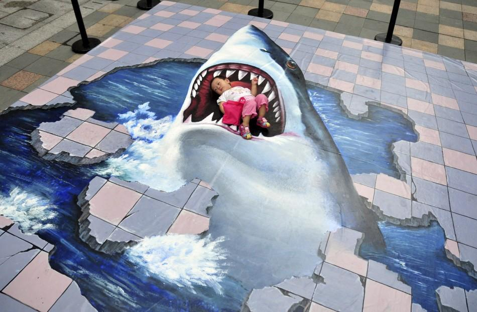 A child lies on a piece of 3D pavement artwork featuring a shark as she poses for a photograph for her family inside a shopping mall in Fuzhou