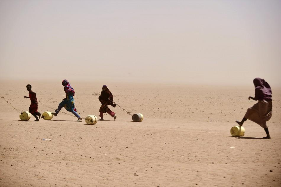 People roll and drag water containers in Wajir