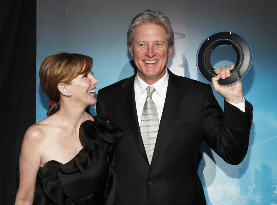 "Cast member Boxleitner holds an Identity Disc as he poses with his wife Gilbert at the world premiere of the film ""TRON: Legacy"" in Hollywood"