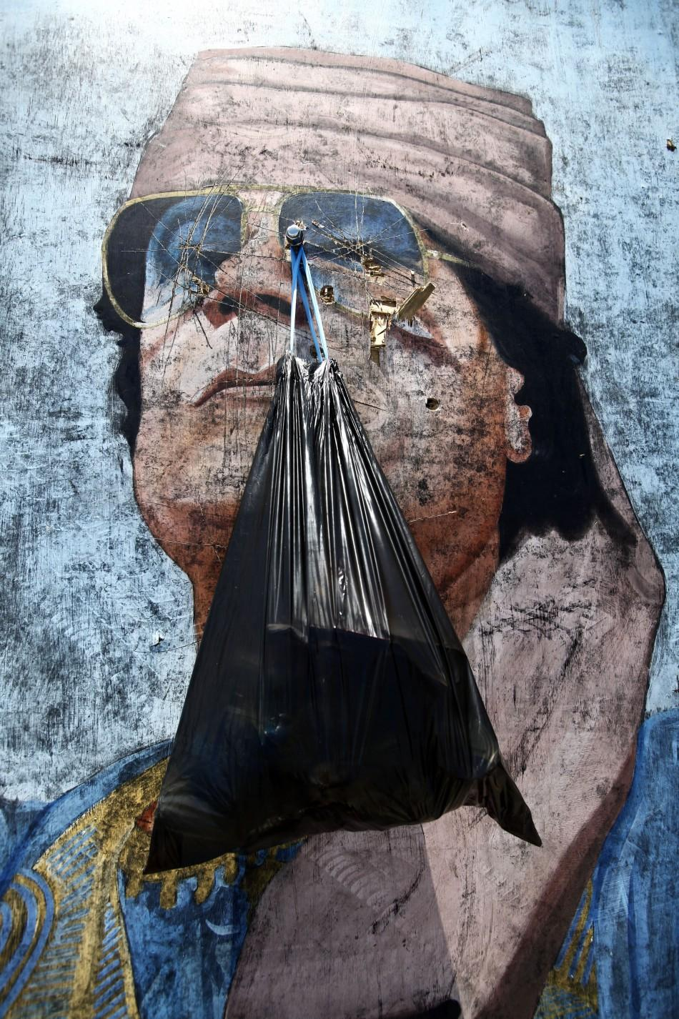 A garbage bag hangs from a portrait of Muammar Gadhafi in Tripoli