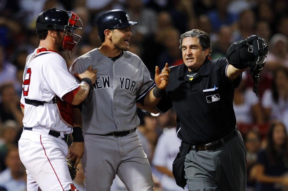 New York Yankees' Cervelli is held back by Boston Red Sox's Saltalamacchia and home plate umpire Capuano after getting hit by a pitch during their MLB American League baseball game in Boston