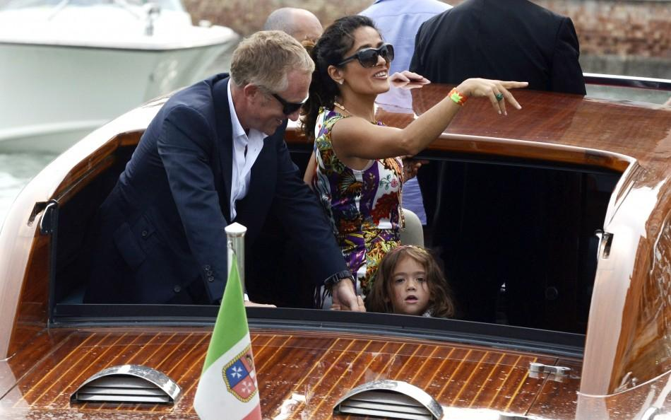 Actress Salma Hayek (C), her husband Francois-Henri Pinault and their daughter Valentina arrive by speedboat to the 68th Venice Film Festival