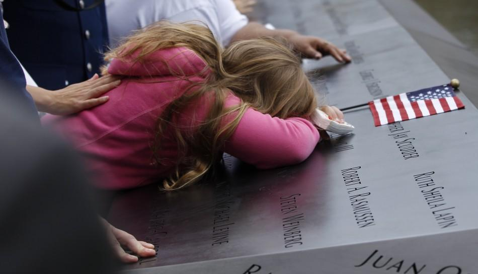 Mourners touch the names of lost loved ones during ceremonies marking the 10th anniversary of the 9/11 attacks on the World Trade Center, in New York