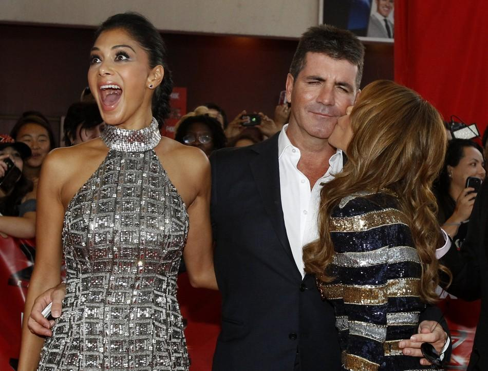 "Paula Abdul kisses the cheek of Simon Cowell as Nicole Scherzinger reacts at the world premiere of the television series ""The X Factor"" at the Arclight Cinerama Dome in Hollywood, California"