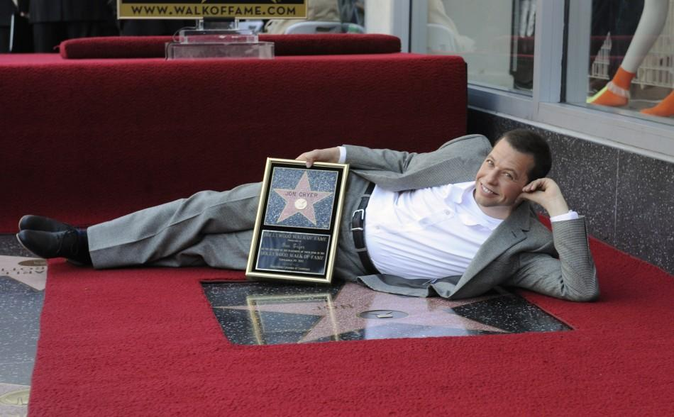 Jon Cryer poses for photographers with his commemorative plaque during a ceremony honoring him with a star on the Hollywood Walk of Fame in Los Angeles