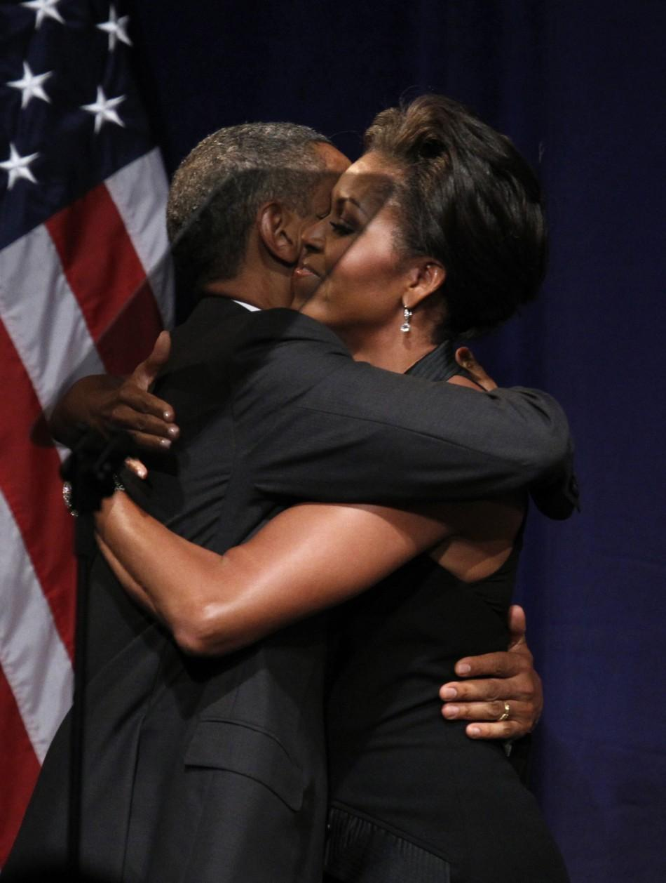 U.S. President Barack Obama embraces first lady Michelle Obama after she introduced him to speak at a fund raiser in New York September 20, 2011.