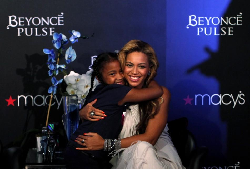 Singer Beyonce hugs a girl during an event to debut her newest fragrance, Beyonce Pulse, at Macy's store in New York