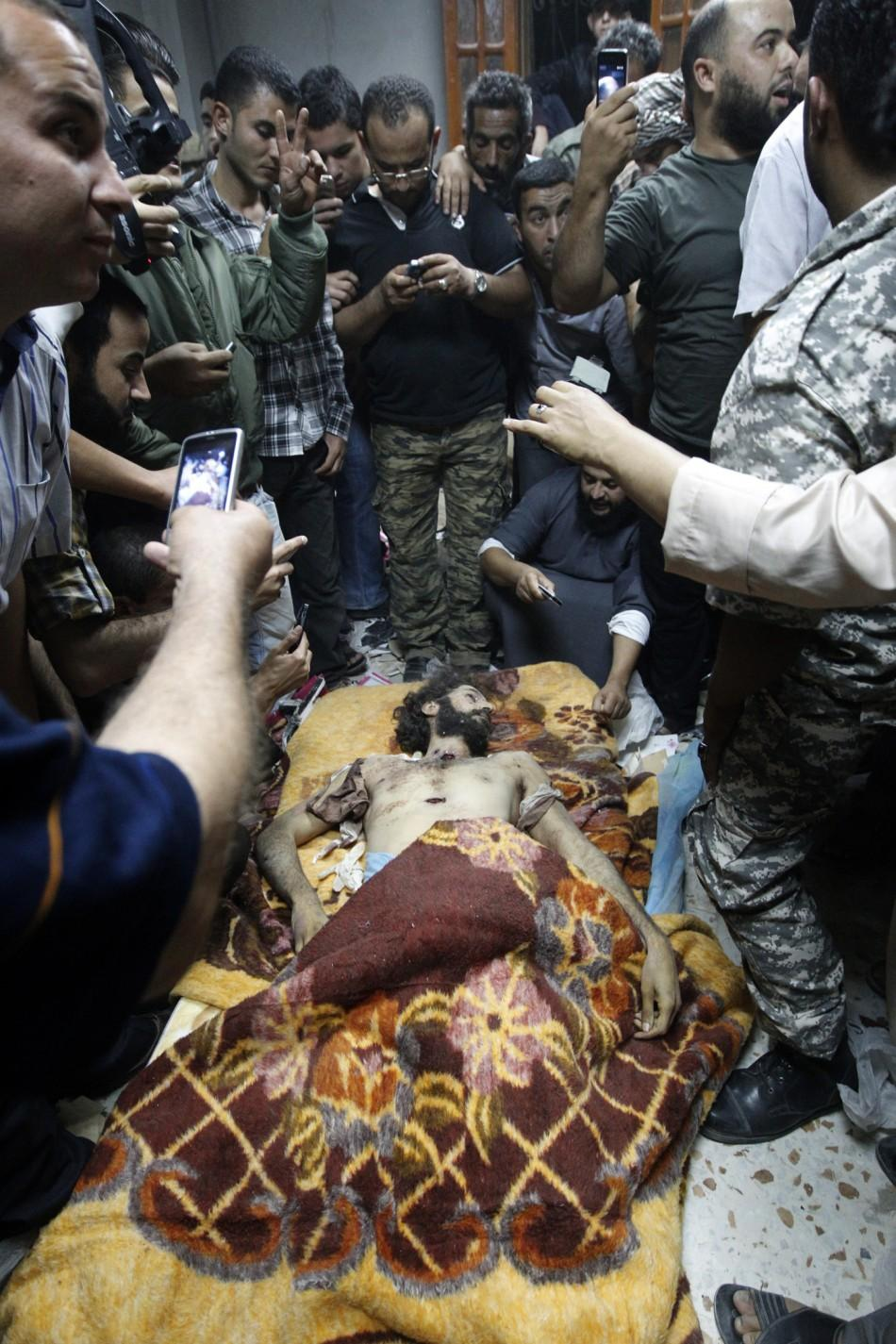 Men stand around and take pictures of Mo'tassim Gaddafi, son of Muammar Gaddafi, in Misrata after being captured and killed during clashes with anti-Gaddafi fighters in Sirte October 20, 2011.