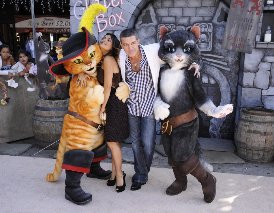 "Cast members Antonio Banderas (R) and Salma Hayek (L) pose with characters at the premiere of the animated film ""Puss In Boots"" in Los Angeles"