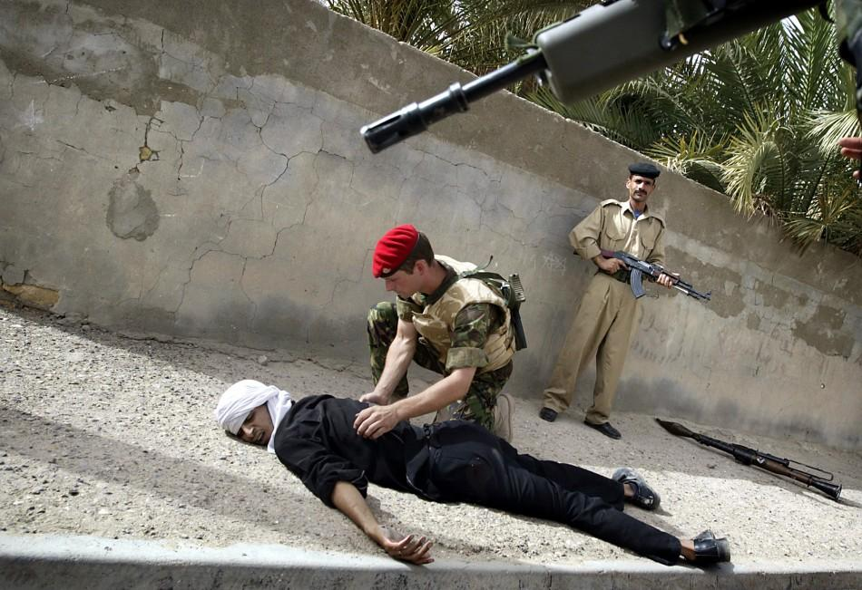 An Iraqi policeman keeps an eye on the crowd as a British military policeman searches a gunman who was shot by coalition soldiers after he threatened a joint police patrol with a rocket launcher in the Hayaniya neighbourhood of Basra May 20, 2003