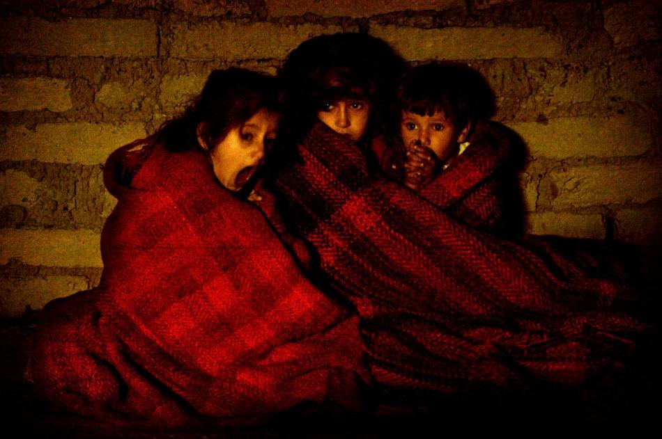 Terrified Iraqi children protect themselves from the cold after they're taken outside their house during a pre-dawn raid in a suburb of Baquba November 16, 2003. [Looking for members of a suspected terrorist cell who attacked coalition forces, troops
