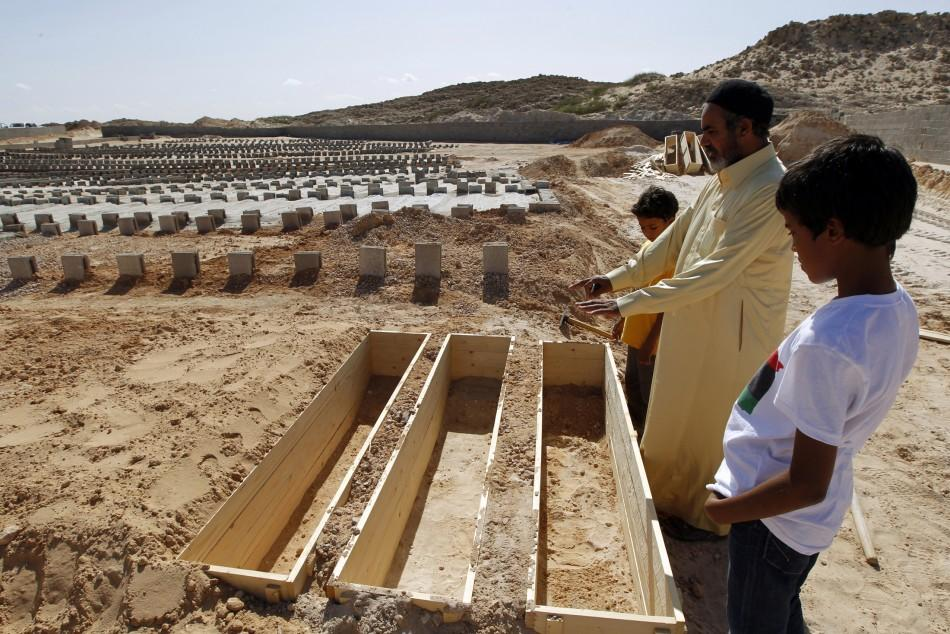 A man looks at empty coffins in a cemetery where soldiers loyal to former Libyan leader Muammar Gaddafi are being buried in Misrata October 25, 2011.