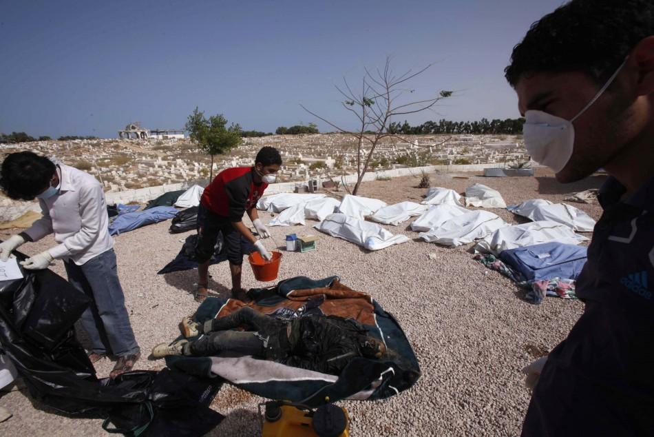 Men inspect about 45 bodies found in Bani Hawal cemetery in Sirte October 25, 2011.