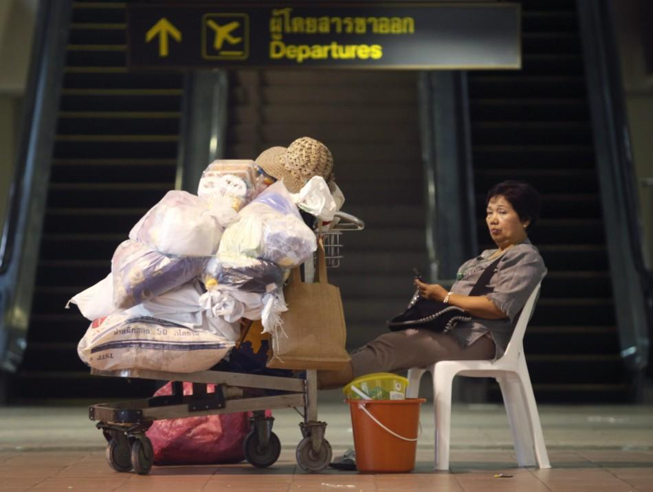 A flood victim waits for her transportation to be relocated to a new evacuation centre, at Don Muang Airport in Bangkok