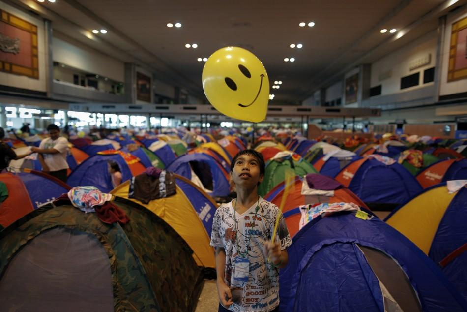 A boy, evacuated from area affected by floods, plays with a balloon at the collective shelter at the Don Mueang airport in Bangkok