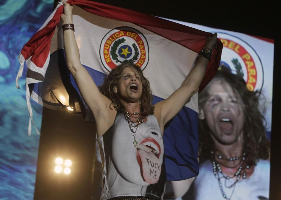Steven Tyler of Aerosmith holds a Paraguayan national flag during a concert on the first stop of their Latin America tour at the Jockey Club in Asuncion October 26, 2011.