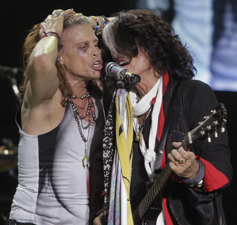 Steven Tyler (L) and Joe Perry of Aerosmith perform during a concert on the first stop of their Latin America tour at the Jockey Club in Asuncion October 26, 2011