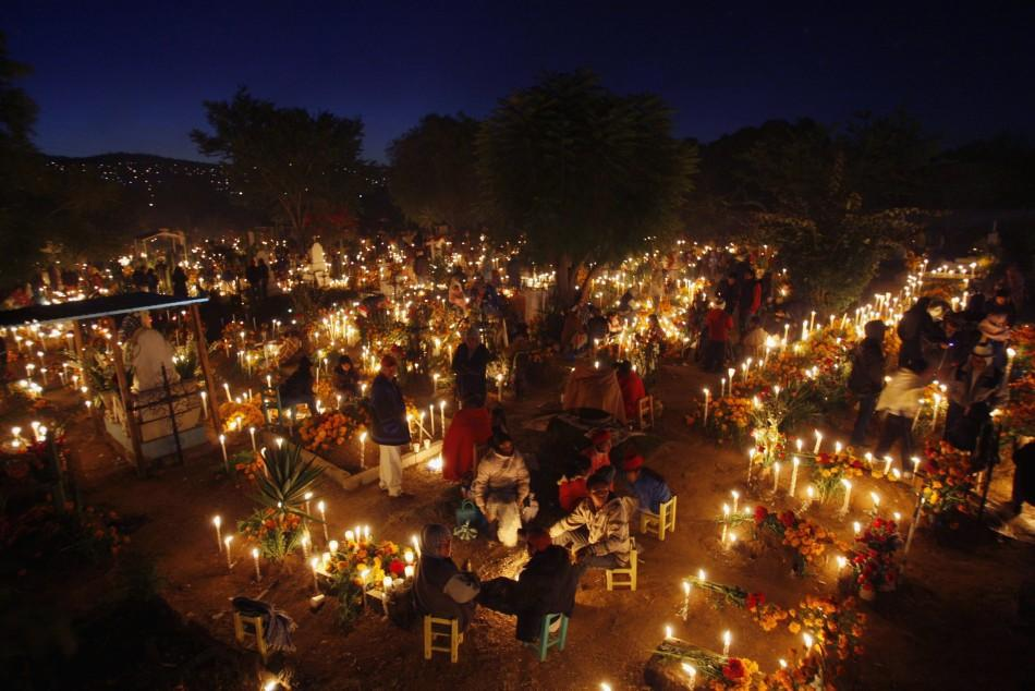 People stand amongst graves decorated with flowers and lit candles at a cemetery in Oaxaca November 1, 2011. Each year, Mexicans celebrate the Day of the Dead by preparing meals and decorating graves of deceased relatives and friends