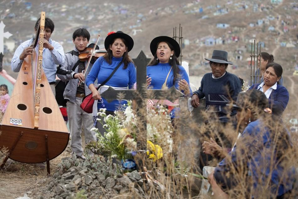 Andean singers perform in front of a grave during the Day of the Dead celebrations in Nueva Esperanza cemetery in Villa Maria, Lima November 1, 2011. Each year people visit the cemetery, one of Latin America's largest, to honour the dead