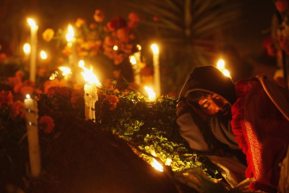 A man sleeps on the grave of a family member decorated with flowers and lit candles at a cemetery in Oaxaca November 1, 2011.