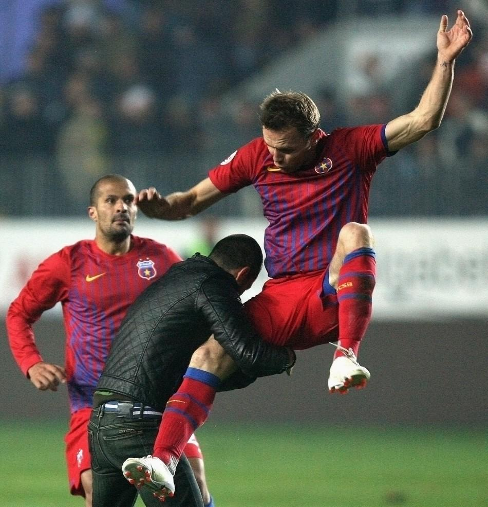 Novak Martinovic of Steaua Bucharest (R) kicks a Petrolul supporter after he attacked two teammates during their ill-tempered league match in Ploiesti, October 30, 2011.