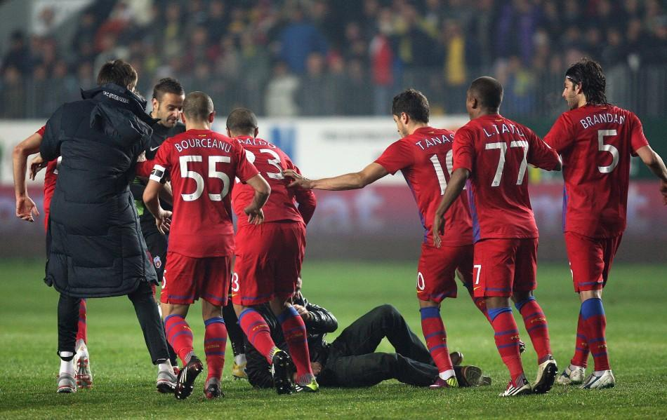 Steaua Bucharest players kick a Petrolul supporter after he attacked two teammates during their ill-tempered league match in Ploiesti