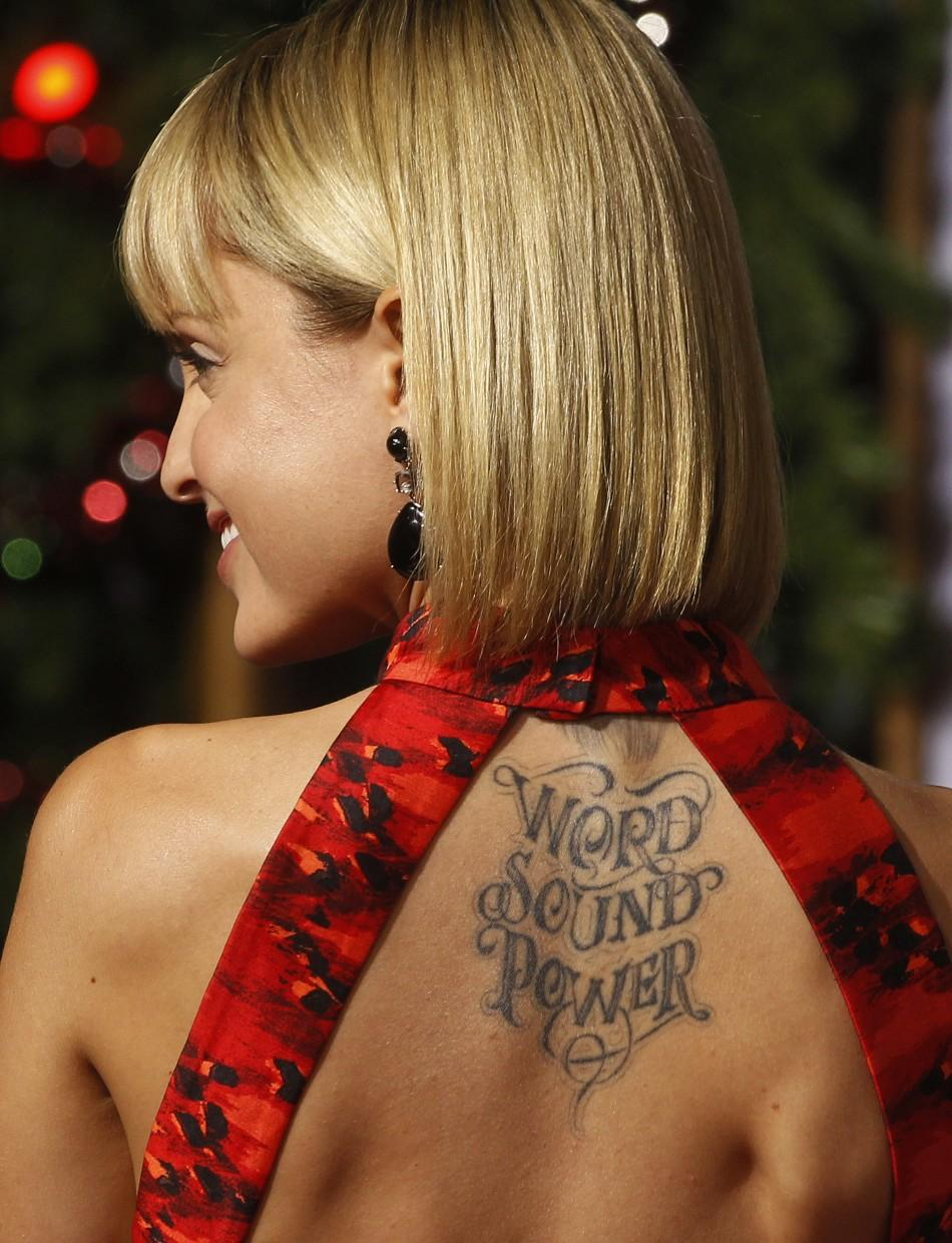 "Actress Mena Suvari poses showing her tattooed back at the premiere of the new film ""A Very Harold & Kumar 3D Christmas"" in Hollywood"
