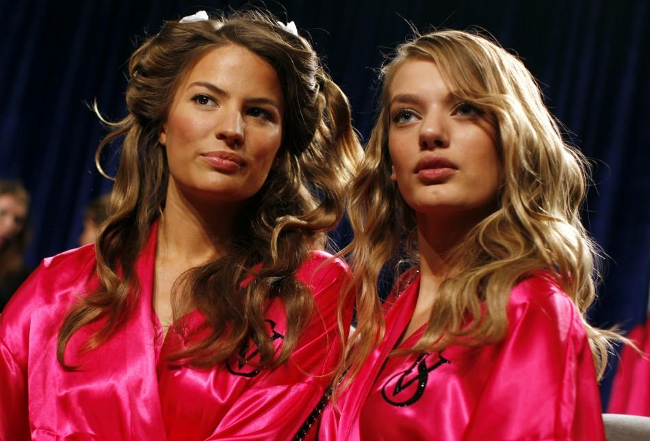 Models Lily Aldridge from the U.S. (L) and Bregje Heinen from the Netherlands (R) get their hair and makeup done backstage before the 2011 Victoria's Secret Fashion Show in New York, November 9, 201