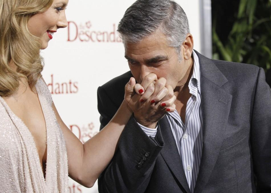 "Cast member George Clooney kisses the hand of actress Stacy Keibler at the premiere of ""The Descendants"" at the Samuel Goldwyn Theater in Beverly Hills, California"