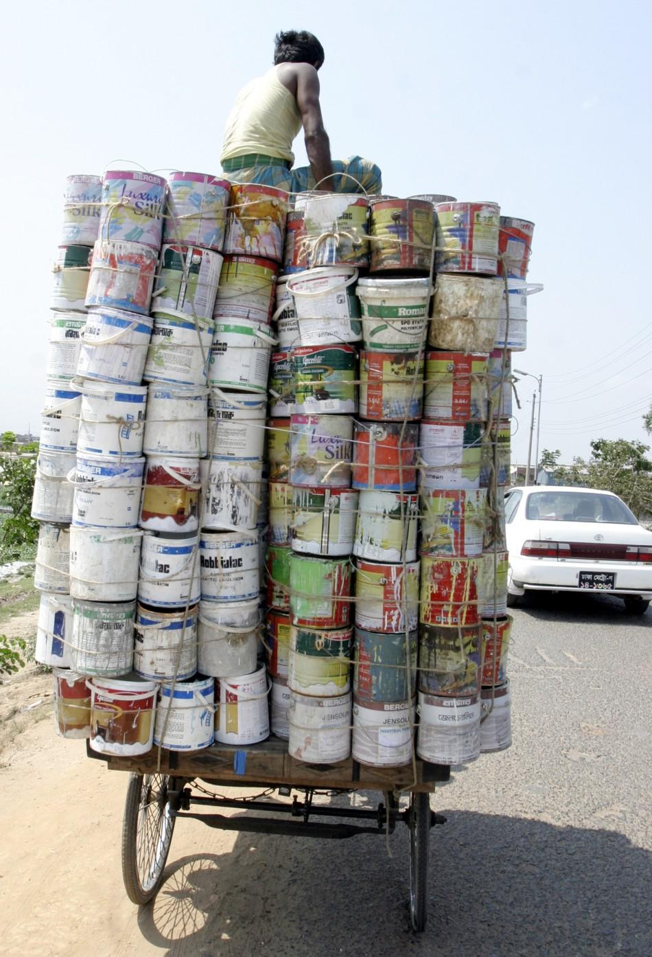 A man transports used pots of paints to sell in a market in Dhaka