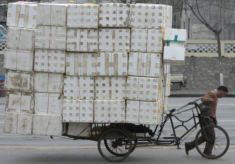 A migrant worker pulls a cart loaded with discarded plastic foam for recycling in Nanjing