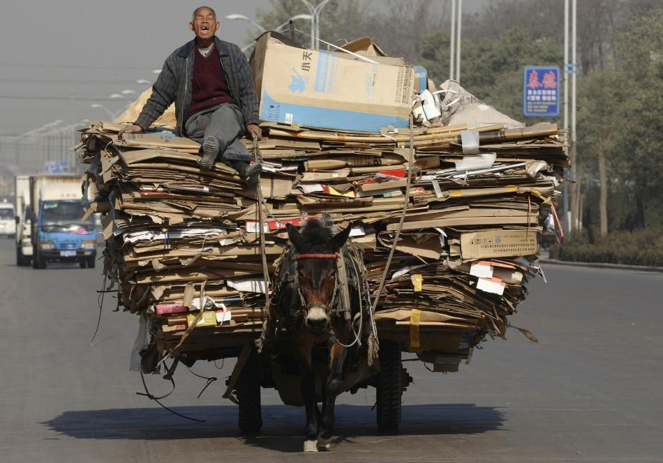 A man yawns while riding on a donkey cart loaded with recyclable materials in Changzhi