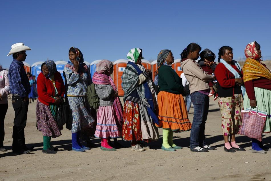 Tarahumara Indians stand in line to receive a government donation of food in Guachochi