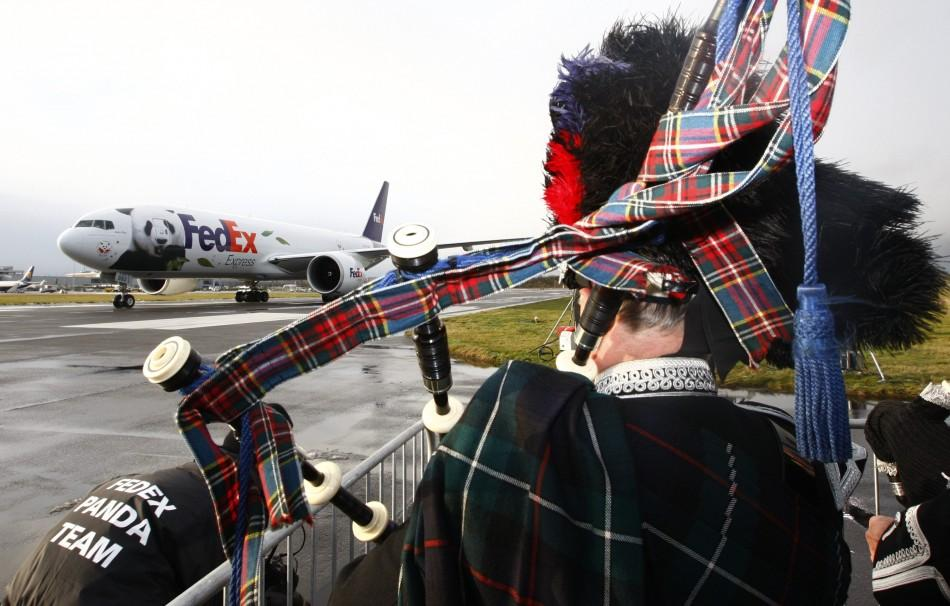 A bagpiper watches as the FedEx Panda Express aircraft carrying two giant pandas taxis along the runway at Edinburgh airport in Scotland