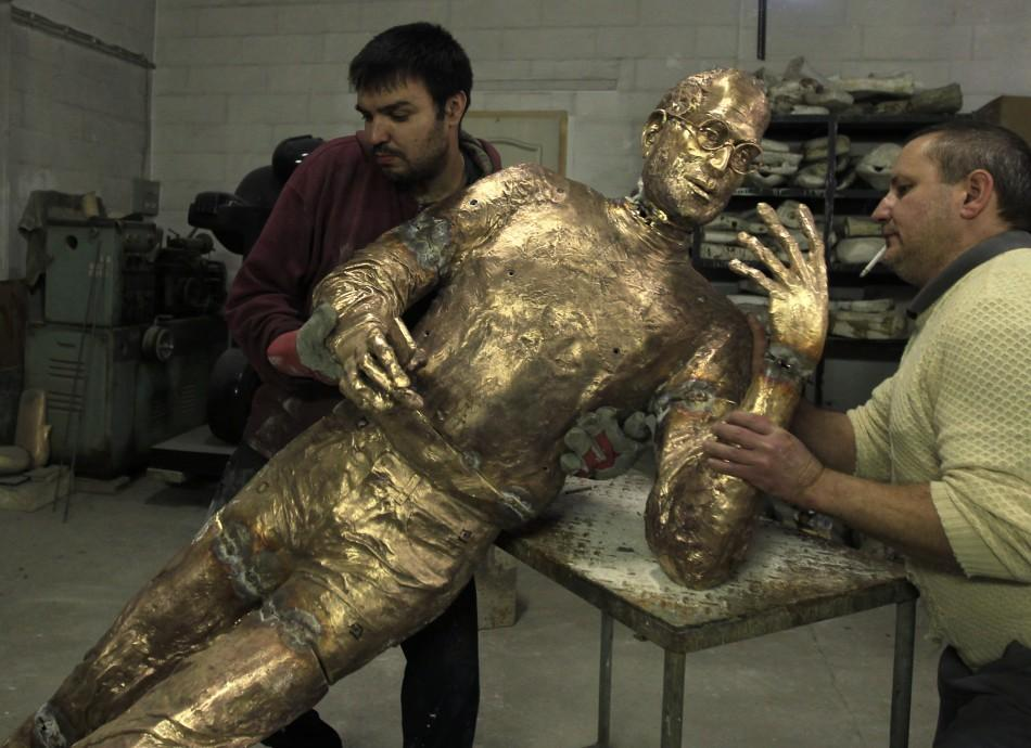 Assistants of Hungarian sculptor Erno Toth adjust his latest work, a bronze statue of late Apple CEO Steve Jobs, in Budapest