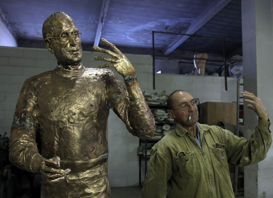 Assistant to Hungarian sculptor Erno Toth mimics the pose of the sculptor's latest work, a bronze statue of late Apple co-founder Steve Jobs, in Budapest