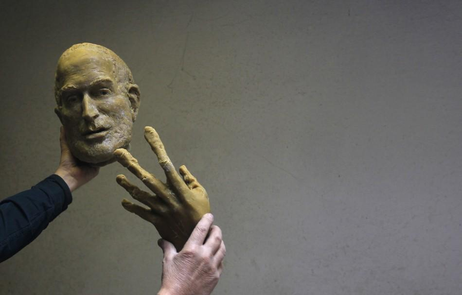 Hungarian sculptor Erno Toth holds up a face and a hand of a wax model for a new bronze statue of late Apple co-founder Steve Jobs in Budapest