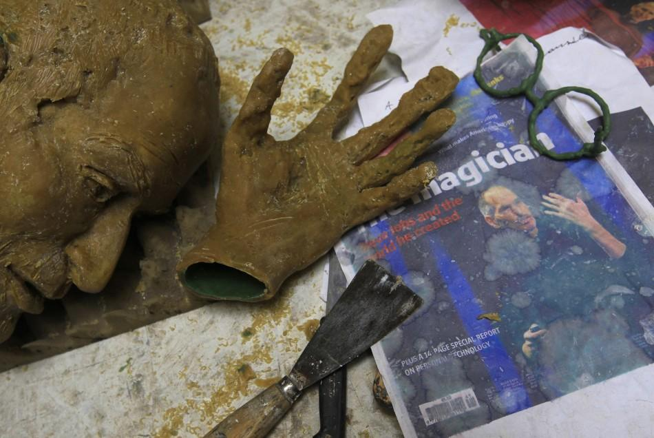 Parts of wax model for new bronze statue of late Apple co-founder Steve Jobs are seen near magazine cover with picture of Jobs in studio of Hungarian sculptor Toth in Budapest