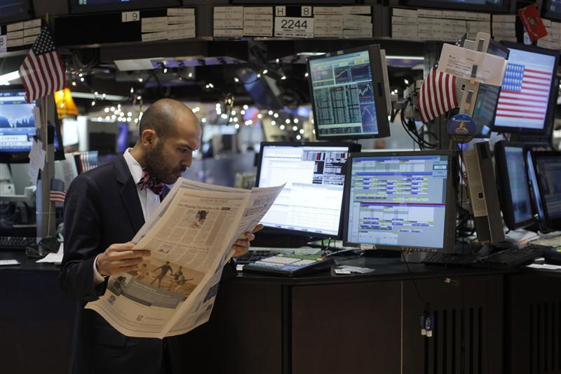 A trader reads a newspaper on the floor of the New York Stock Exchange in New York